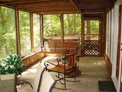 screened porch off living room with table and chairs and hot tub on deck