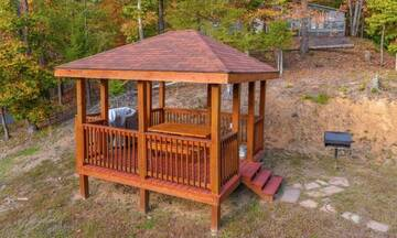 Rental cabin's Gazebo with picnic table, gas grill and charcoal grill.