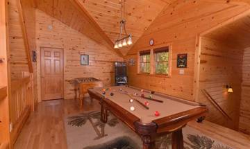 Rental cabin's loft game room with pool table, arcade game, and Foosball table.