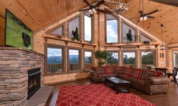 Log cabin with large living room, stacked stone gas log fireplace and large windows looking over endless views of the Tennessee Smoky Mountains.