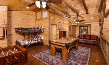 Your log cabin rental's loft game room also offers a full bunk bed and sleeper sofa.