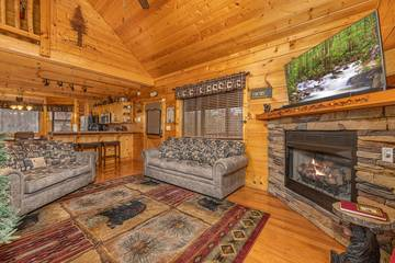 Relaxing Pigeon Forge cabin rental living room with gas log fireplace at 4 Paws cabin.