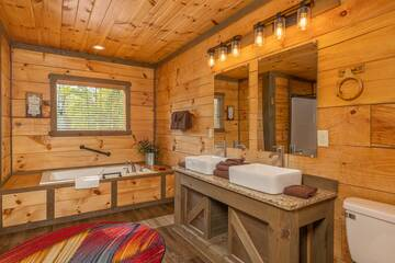 Cabin's master bedroom bath with Jacuzzi tub and dual farm sinks.