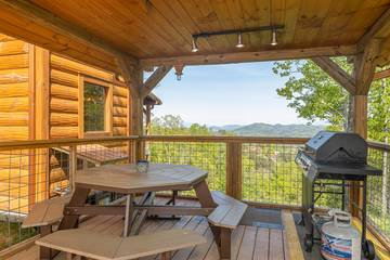 Pigeon Forge area cabin with picnic table and gas grill on the porch.